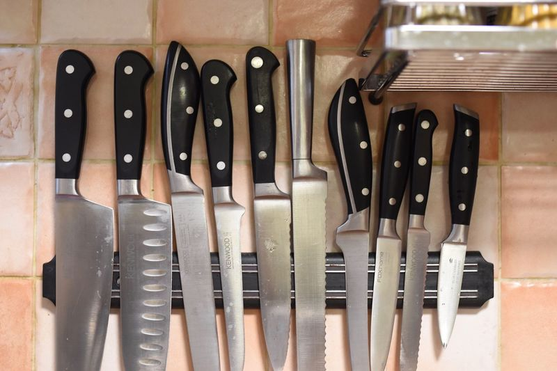 Close-up of knives against tiled wall in kitchen