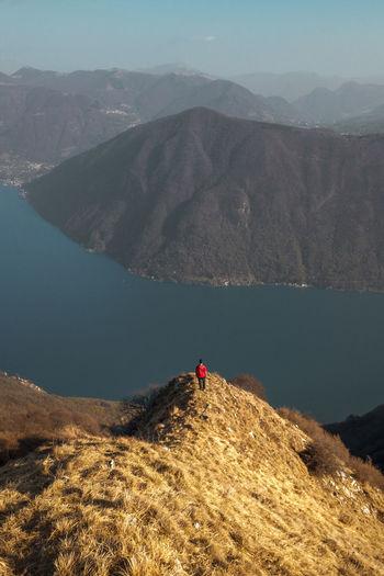 Rear view of man standing on mountain ridge looking at lake