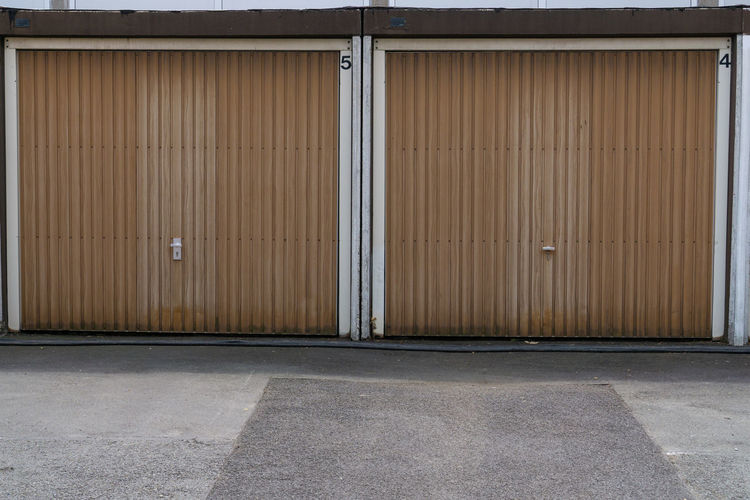 Brown wooden garage doors on a sunny day Garage Door Wood Home Wooden House Parking Background Wall Brown Architecture Front Floor Cement Texture Residential  Dark Vintage Retro Building Decor Urban Textured  Panel Entrance Built Structure Iron Building Exterior Closed Metal Outdoors