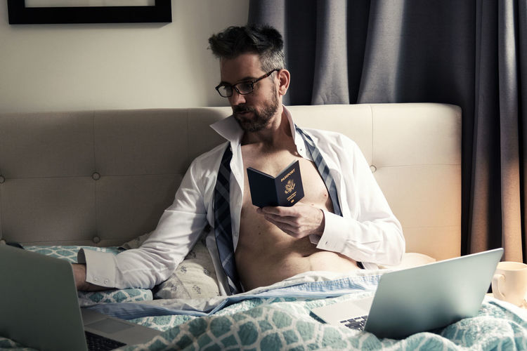 Man in bed leaning against headboard holding passport using computers to plan travel