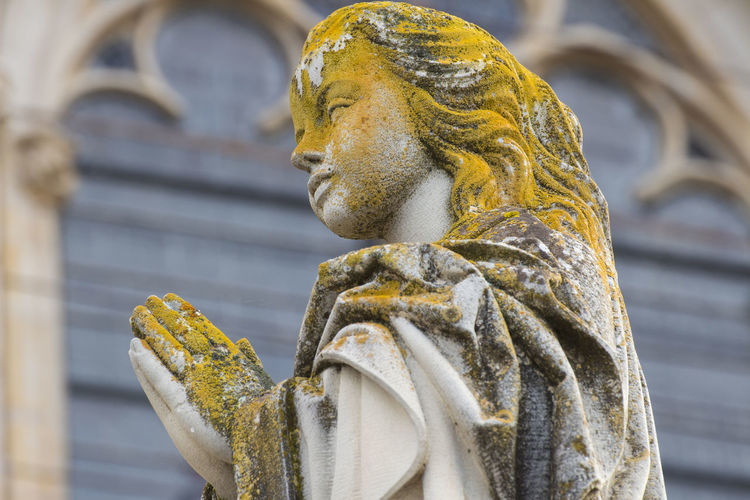Low Angle View Of Female Statue Against Building
