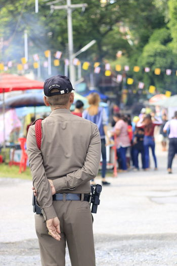 Three Quarter Length Focus On Foreground Real People People Day Incidental People Rear View Clothing Standing Men City Security Protection Uniform Outdoors Walking Lifestyles Occupation Street