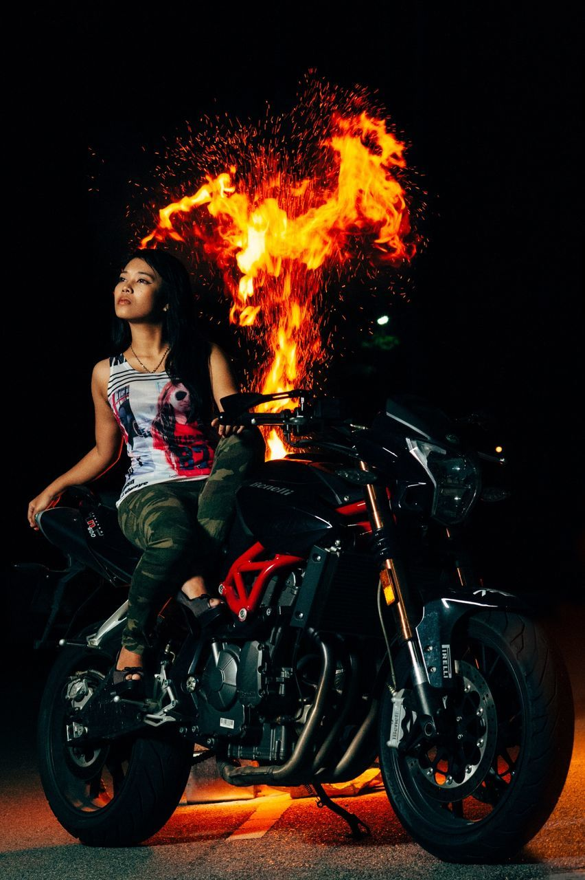 one person, night, real people, motorcycle, young adult, biker, transportation, young women, illuminated, outdoors, lifestyles, full length, people