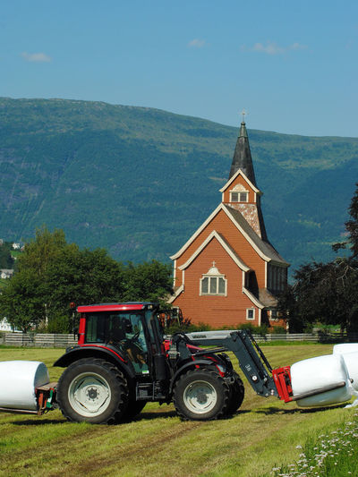 Tractor Church Agricultural Machinery Agricultural Equipment Land Vehicle Building Place Of Worship Mountain Tree Sky Building Exterior Architecture Built Structure Day Nature Land Outdoors No People Church Steeple Tractor Farm Hay Bale Farmland Farming