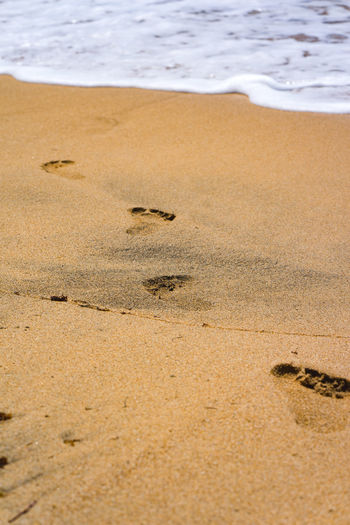 Barefoot step prints in sand of a beach. Beach Life Beach Surfers Paradise Hang Loose Travel Time To Reflect Time Out Vacation Background Water Wave Sea Beach Sand Dune Sand Low Tide Sky Animal Themes Paw Print FootPrint Track - Imprint Sandy Beach Tire Track Calm Tide Surf Shore