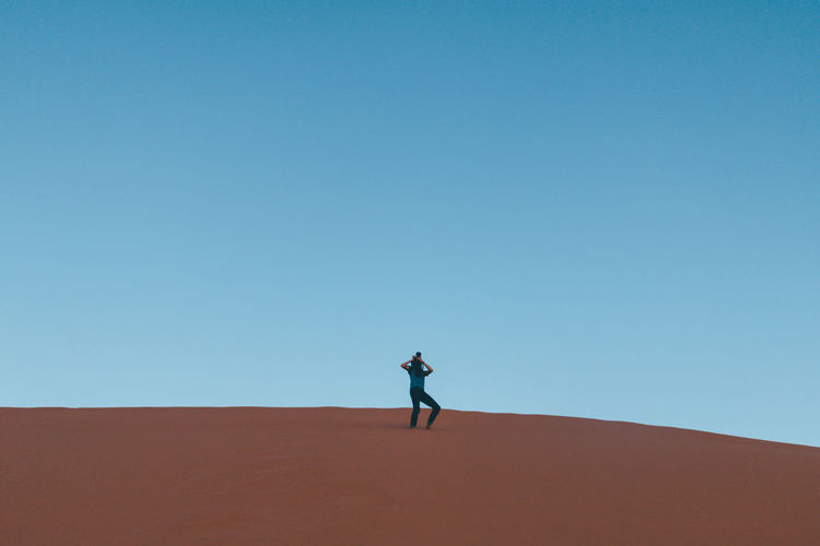 Man on sand dune against clear sky