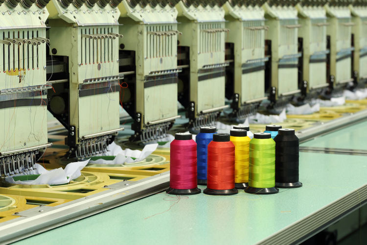 Machine Embroidery Sewing Textile Thread Industry Background Cotton Factory Manufacturing Clothing Threads Spool Reel Fashion Material Sew Tailor Colorful Polyester Craft Manufacture Bobbin Shop Clothes Fiber Fabric Color Wool SPOOLS Production Needle Work White Equipment Product Industrial Needlework Coil Orange Green