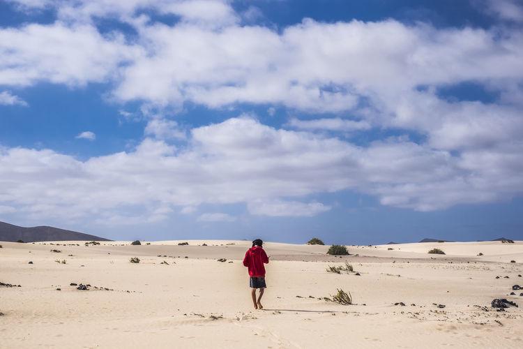 Rear view of teenage boy walking at desert against cloudy sky