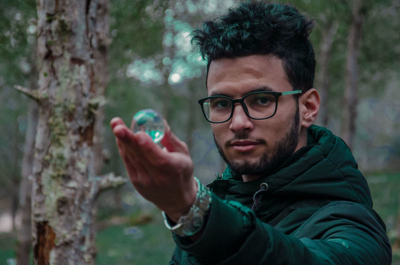 Portrait of young man holding crystal ball in forest