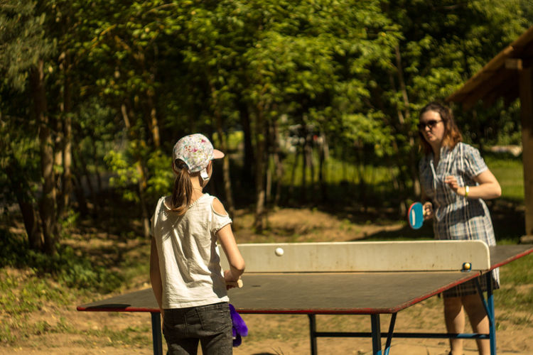 Mother and daughter playing table tennis at park during sunny day