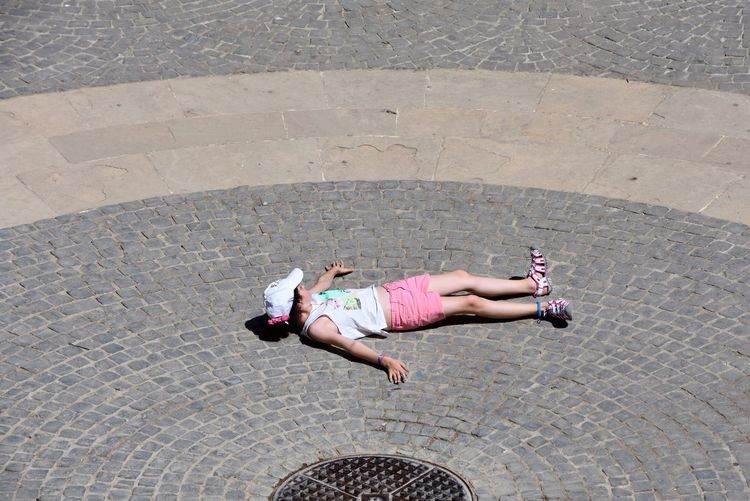 High angle view of girl lying on cobbled street