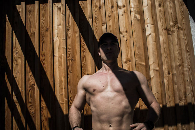 Shirtless Muscular Man Standing Against Wooden Wall During Sunny Day
