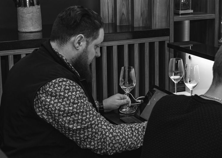 Side view of man holding wineglasses on table in restaurant
