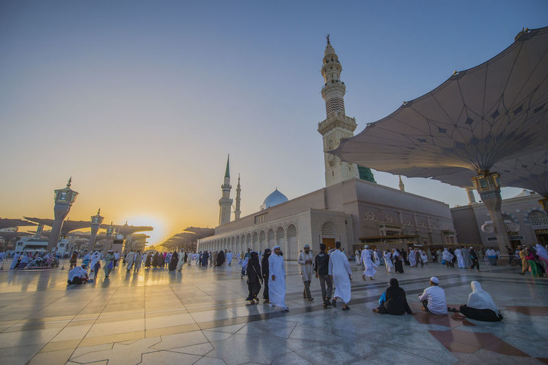 Muslims marching in front of the mosque of the Prophet Muhammad, Nabawi mosque during sunset Arabia Green Dome Hajj Islam Islamic Mosque Muslim Muslims Nabawi Nabawi Mosque Prophet Muhammad Religion Reward Saudi Arabia Sin, Sunset Umrah Vintage