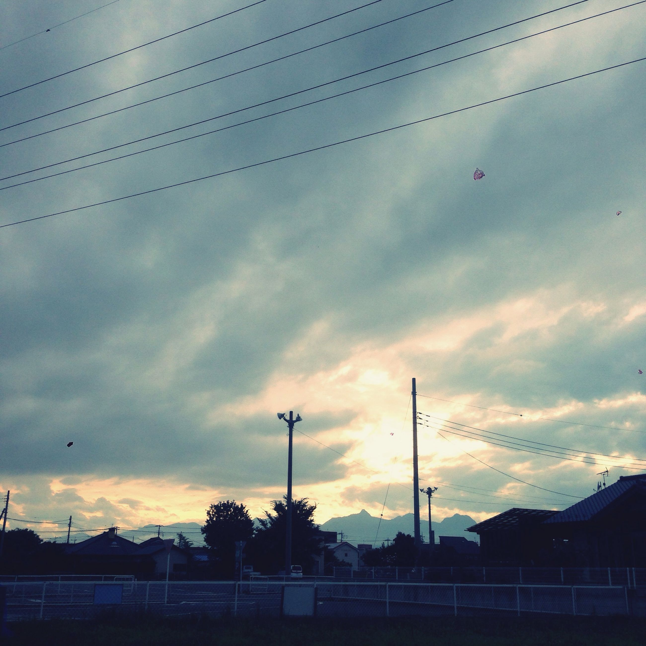 sky, cloud - sky, sunset, silhouette, street light, low angle view, cloudy, power line, cloud, bird, electricity pylon, connection, built structure, dusk, scenics, nature, beauty in nature, electricity, outdoors, architecture