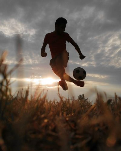 Man playing soccer on field against sky during sunset