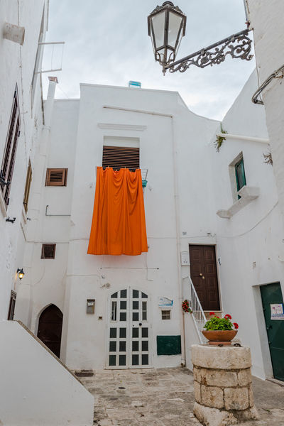 Not everything is white in Ostuni! Backyard Vacations Architecture Building Exterior Built Structure Day Drying Hanging Italy Low Angle View No People Orange Color Outdoors Potted Plant Residential Building Summer Tourism Travel Destinations White Window Mix Yourself A Good Time