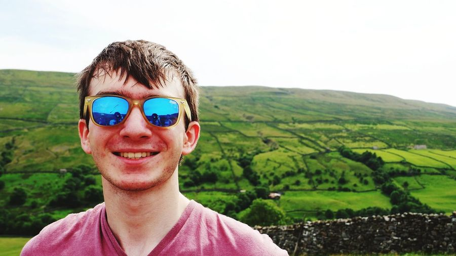 Portrait Of Smiling Young Man Wearing Sunglasses With Landscape In Background
