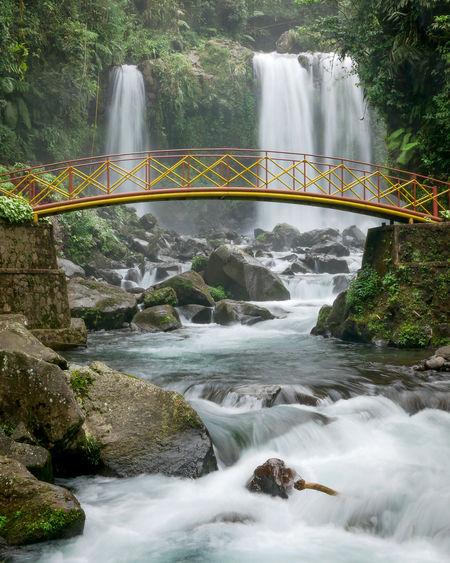 Bridge over river flowing through rocks