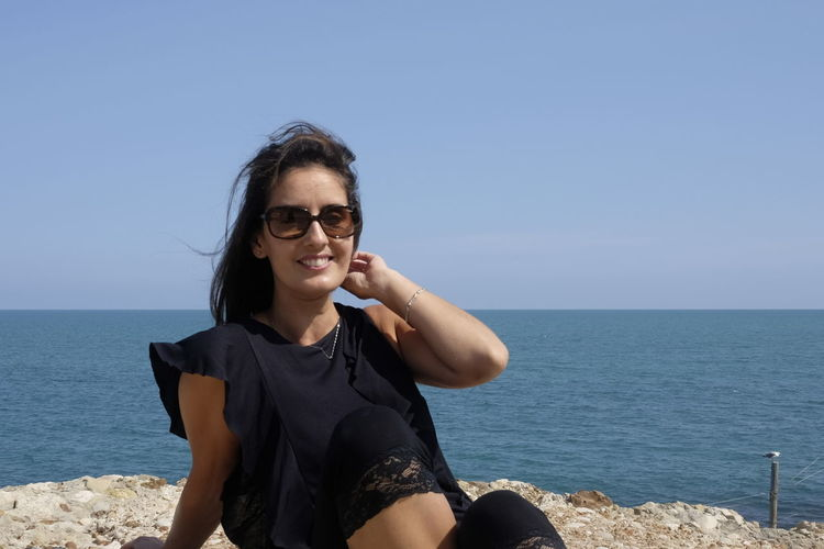 Portrait of smiling young woman wearing sunglasses sitting at beach against clear sky