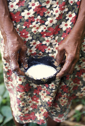 Midsection of woman holding sap in bowl