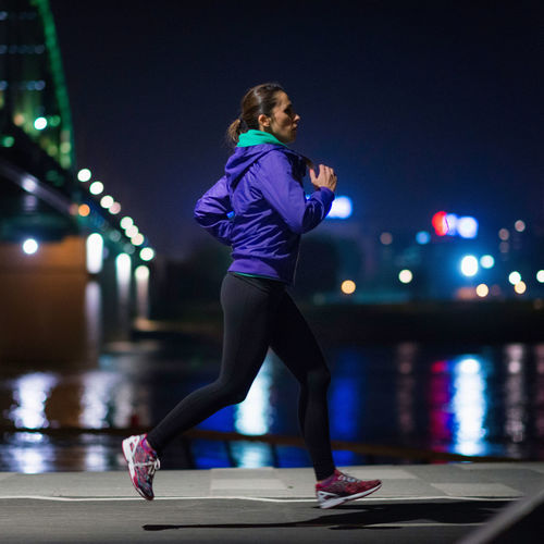 Side view full length of woman running by river on footpath at night