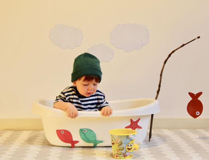 Baby boy in bathtub against wall