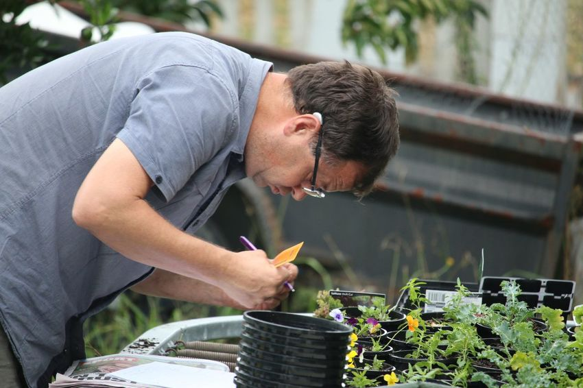 A photo of a man doing experimental work on plants. Casual Clothing Close-up Day Experiment Father Fertiliser Focus On Foreground Garden Interesting Leisure Activity Lifestyles Meal Outdoor Person Pots Sitting Standing Waist Up