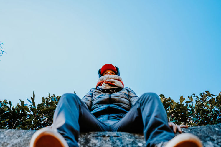 Low section of man sitting against clear sky