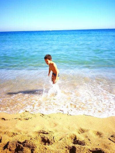 Shirtless boy playing with water at seashore