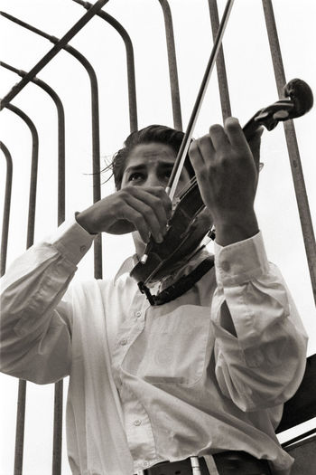 Low angle view of man playing violin against railing