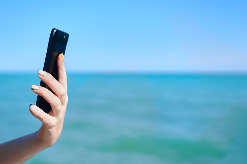 Midsection of man using mobile phone against blue sky