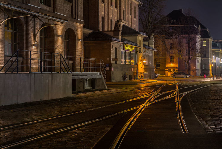 Railroad tracks by buildings in city at night