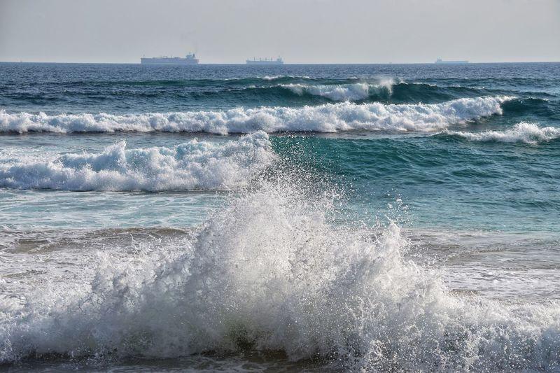 Shipping and surf Sea Water Motion Horizon Over Water Wave Sky Horizon Outdoors Breaking Splashing