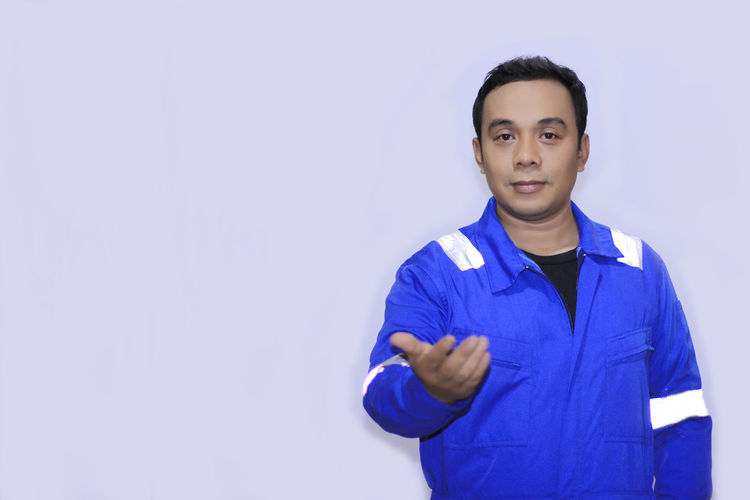 Young Asian Engineer with Blue wearpack Looking At Camera Portrait One Person Front View Studio Shot Standing Waist Up Copy Space Confidence  Young Adult Blue Indoors  Casual Clothing Clothing Gesturing Lifestyles Young Men Serious Adult Purple Finger