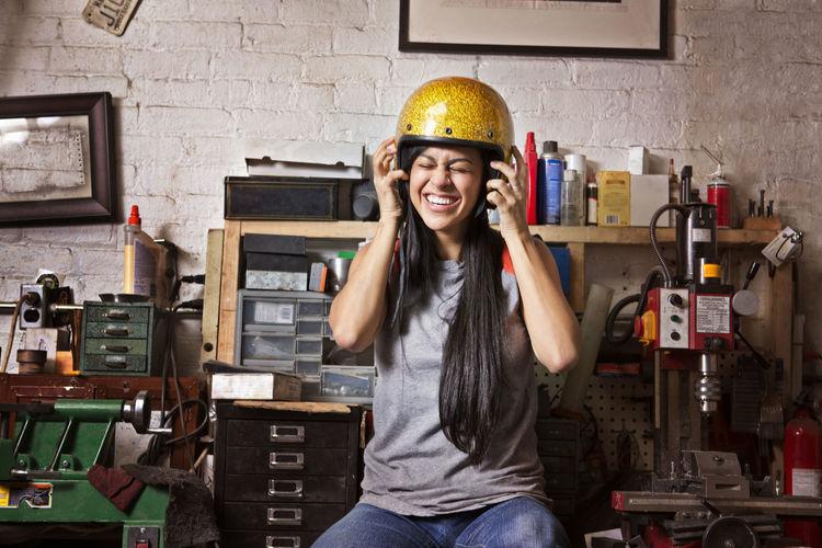 Cheerful female owner wearing helmet in auto repair shop