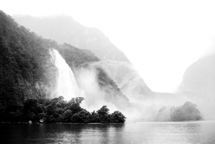 Scenic view of waterfall against sky in milford sound, new zealand