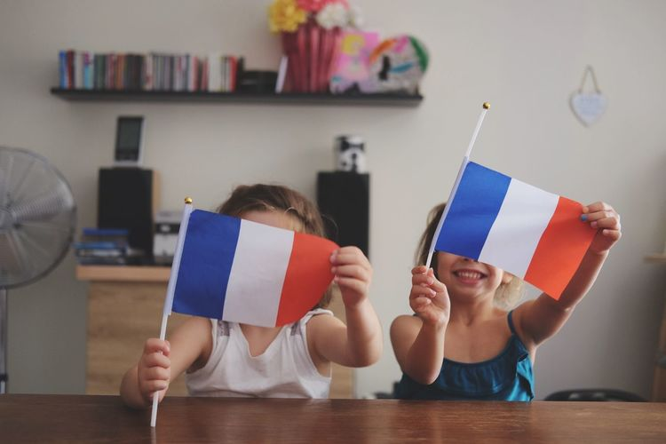 Siblings holding flags at home