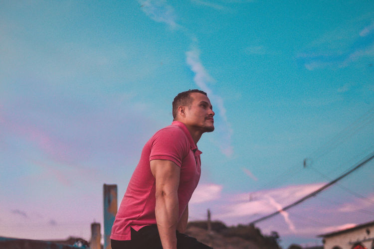 Side view of young man standing against blue sky