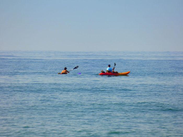 Men Canoeing In Sea Against Sky