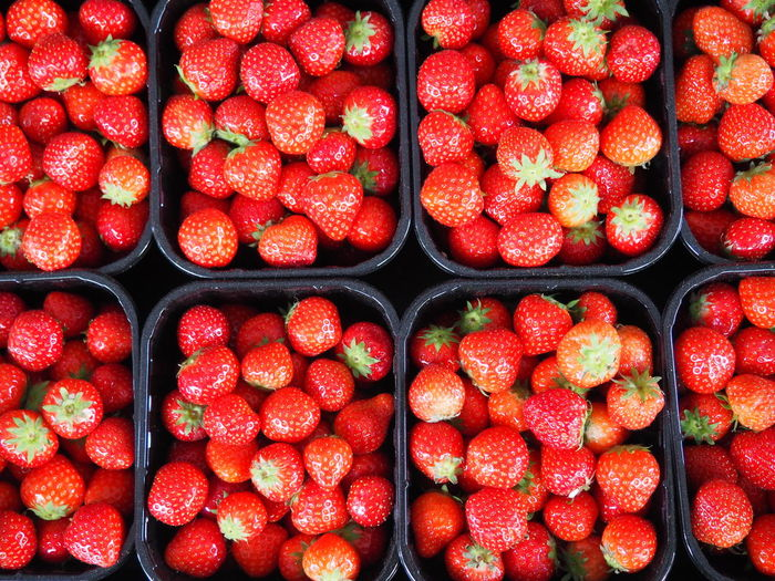 Full frame shot of strawberries in containers for sale at market stall