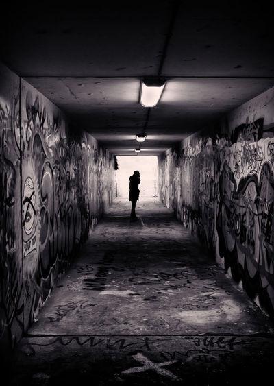 Silhouette woman standing in tunnel along graffiti walls