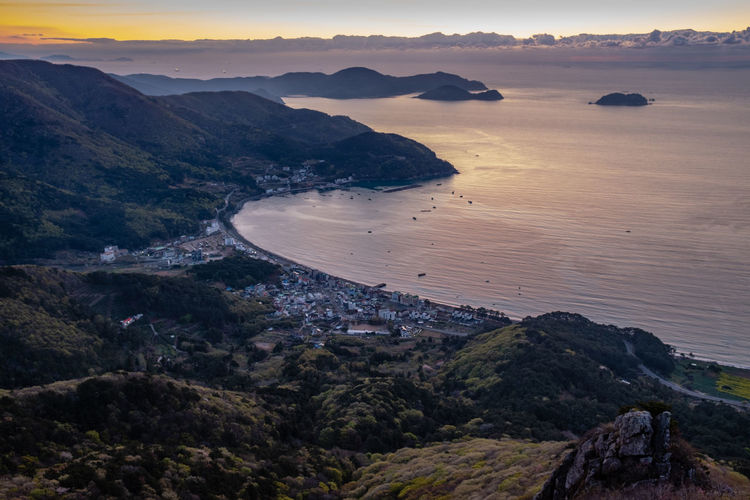 Aerial view of seaside villages, mountains, islands, sea and sky during sunrise Scenics - Nature Beauty In Nature Water Mountain Tranquility Land Tranquil Scene Sea Sky Nature High Angle View Sunset Non-urban Scene Beach No People Idyllic Environment Outdoors Rock