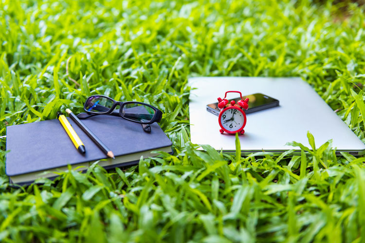 Book with smart phone and eyeglasses on field