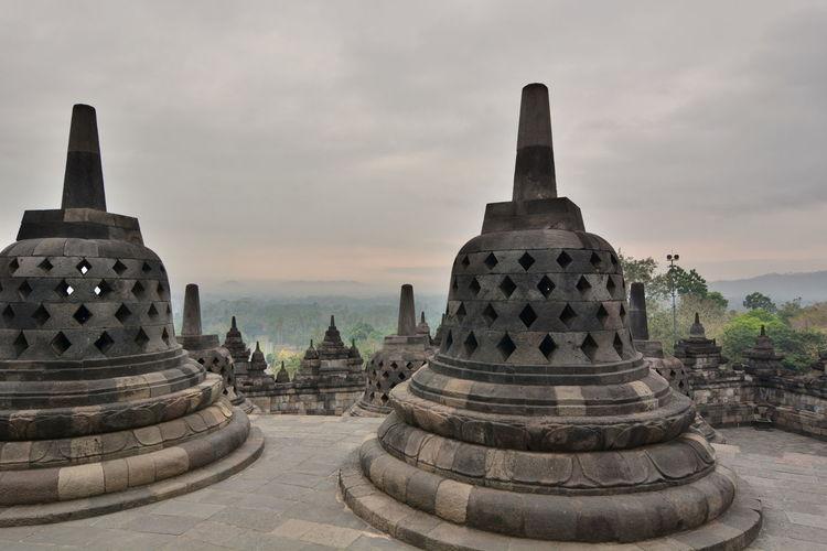 Stupas at temple against sky