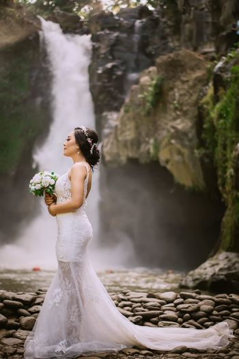 Close-up of woman standing on rock by waterfall