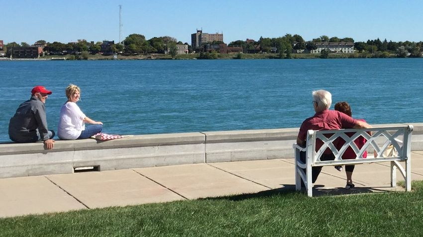Riverside Chat St. Clair River River Socializing Leisure Activity Lifestyles Water Togetherness Casual Clothing Bonding Sunlight Tree Sitting Love Clear Sky Person Architecture Building Exterior Day Sunny Sky Friendship Blue People And Places Snap a Stranger Break The Mold