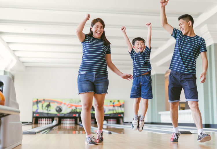 Asian family having fun at bowling club Family Happiness Happy Winning Arms Raised Blowing Bowling Bowling Alley Boys Casual Clothing Child Childhood Emotion Group Of People Happiness Human Arm Human Limb Indoors  Innocence Jumping Lifestyles Males  Men Togetherness Women