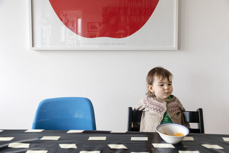 Portrait of boy sitting on table at home