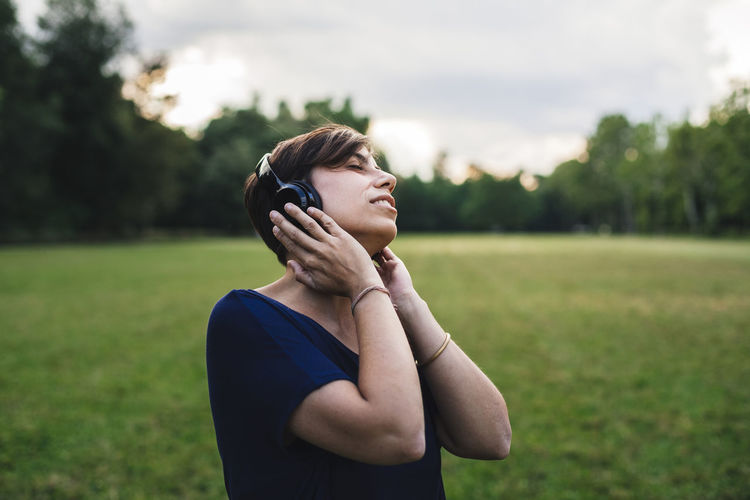 Young adult woman listening to music at the park One Person Waist Up Young Adult Leisure Activity Casual Clothing Eyes Closed  Grass Plant Standing Day Front View Nature Emotion Adult Lifestyles Field Outdoors Contemplation Freedom Millenials Headphone Music Relax Park Break